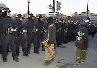 OTTAWA , November 17th 2001 FILE PHOTO<br /> <br /> Two young demonstrators walk in front of Policemen in riot gear standing, on ELGIN street just outside the security perimeter, during the Summit of G-20 Countries in Ottawa on Saturday, November 17, 2001. <br /> <br /> Police  used tear gas, concussion grenade's and pepper spray in their attempt to repel the protestor's from entering the security perimeter.<br /> <br /> The  G-20 meeting , where central bank chiefs and finance ministers from rich and poor nations discuss topics such as ; terrorism funding, economy slowdown and 3rd world nation's debt was initially scheduled for september in India,but  postponed  to  November 16th to 18th, 2001 and is beeing hosted by G-20 Chair ;  Canada Minister of Finance ;  Paul Martin.<br /> <br /> <br /> ON SPEC<br /> NOTE l Nikon D-1 jpeg opened with quimage icc profile, saved in Adobe 1998 RGB.