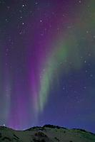 Aurora borealis dances over Slope mountain at the start of the Arctic coastal plains. Blue light of evening dusk silhouettes the mountain, Arctic Alaska