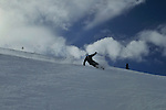 A skier carving in a snowy bowl leaves a snowy wake at Snowbasin, Utah.