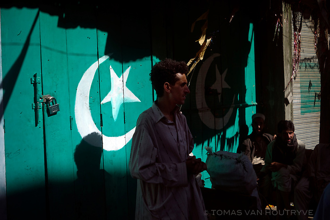 Man stands in front of doors that have been painted with the Pakistani flag in Bahrain in the Swat valley, Pakistan, on Aug. 28, 2010. When the Pakistani Army took back control of villages in the Swat valley that had been occupied by the Taliban, it ordered doors and store fronts to be repainted with the Pakistani flag. Only months after the army got control of the insurgency, massive floods hit the Swat valley.