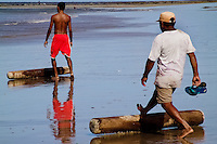 Brazilian fishermen (jangadeiros) work with wooden logs while pushing the boat on the beach of Caponga, Ceará state, northeastern Brazil, 12 March 2004. Jangadeiros, working on a unique wooden raft boat called jangada, keep the tradition of artisan fishing for more than four hundred years. However, being a fisherman on jangada is highly dangerous job. Jangadeiros spend up to several days on high-sea, sailing tens of kilometres far from the coast, with no navigation on board. In the last two decades jangadeiros have been facing up the pressure from motorized vessels which use modern, effective (and environmentally destructive) fishing methods. Every time jangadeiros come back from the sea with less fish.