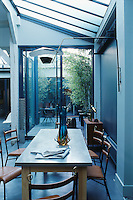 In the dining room the long zinc-topped table is surrounded by Jacques Adneti brass, metal and leather chairs and is flooded with daylight from a skylight running the length of one wall