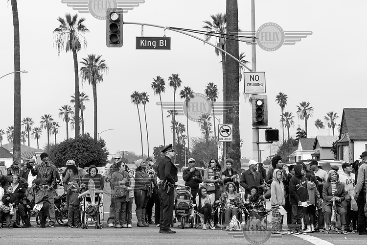 Spectators line the street at a Martin Luther King Day parade.