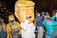 A person wearing a giant head of US president Donald Trump is seen as demonstrators gather in Black Lives Matter Plaza near the White House on the night of Election Day in Washington, D.C., on Tue., Nov. 3, 2020. Election results remained uncertain late into the night and demonstrators were peaceful.