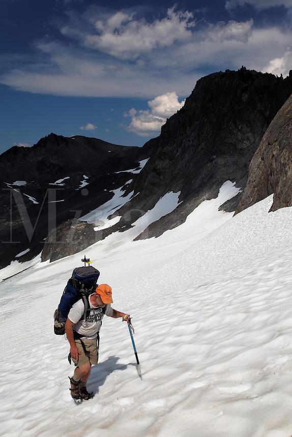 Backpacker climbing snow slope, Bailey Range Traverse, Olympic Mountains, Washington
