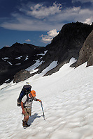 Backpacker climbing snow slope, Bailey Range Traverse, Olympic Mountains, Washington