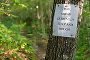 Warning sign along the Holt Trail which climbs to the summit of Cardigan Mountain in Orange, New Hampshire USA. A section of this trail is considered extremely steep and rough.