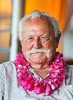 A smiling man wearing a pink plumeria lei on his birthday