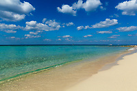 Pristine, deserted white sand beach, with the turquoise and transparent Caribbean Sea, under a blue sky with white clouds, Cozumel Island, Mexico