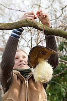 """Mädchen, Kind bastelt einen """"Federspender"""": Weiche Daunenfedern aus altem Kopfkissen werden im Garten den Vögeln in einem regengeschütztem Netz angeboten, die können sie als weiches Nist-Material nutzen. 6. Schritt: Der Federspender wird in einem Busch im Garten aufgehängt"""