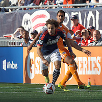 New England Revolution defender Kevin Alston (30) on the attack.  In a Major League Soccer (MLS) match, the New England Revolution (blue/white) defeated Houston Dynamo (orange), 2-0, at Gillette Stadium on April 12, 2014.
