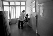 Asmara, Eritrea.November 2002.Birhan Aim Hospital  (Light to the Eye Hospital)..When the 20 minute operation is complete the patient walks out of the operating room and for a few minutes sits silently in a hallway outside the theater.