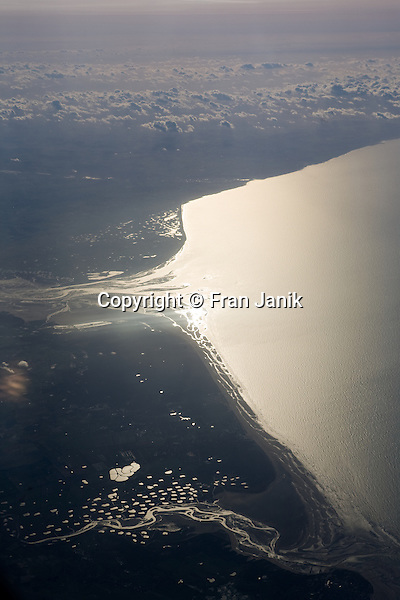 This View of the coast of France was taken from the first class section of an Air France jet during a flight from Paris to Boston. This is a view looking south from the aircraft. Tidal estuaries and man made ponds can be seen reflecting the morning light.