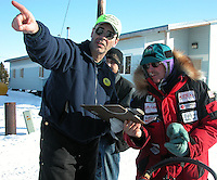 Jon Little.A race volunteer directs Paul Gebhardt to a parking spot as Gebhardt examines the in times for Jeff King and Doug Swingley, Koyuk, March 13, 2006