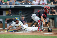 Michigan Wolverines designated hitter Jordan Nwogu (42) slides home during Game 1 of the NCAA College World Series against the Texas Tech Red Raiders on June 15, 2019 at TD Ameritrade Park in Omaha, Nebraska. Michigan defeated Texas Tech 5-3. (Andrew Woolley/Four Seam Images)