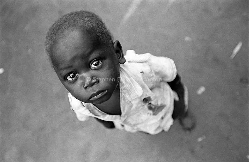 Portrait of a young boy in the bush.  Children are susceptible to many health concerns in Uganda, especially in rural environments. Medical resources to treat complex disease like HIV/AIDS and malaria or even simple concerns like parasites or the flu in rural areas are almost non-existent.  Village Nasamuri. Kamuli District, Uganda, Africa. June 2004 © Stephen Blake Farrington