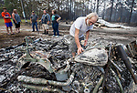 Earl Moss, right, looks over his Harley Davidson Fat Boy motorcycle after wildfires swept through his neighborhood on Ridge Rd in Eastpoint, Fla., Monday, June 25, 2018. Moss' home in the background and many of his neighbor's homes were completely destroyed.  (AP Photo/Mark Wallheiser)