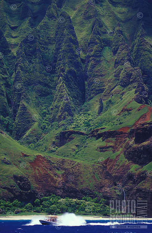 Tour boat blasts into a wave on the Na Pali Coast of kauai