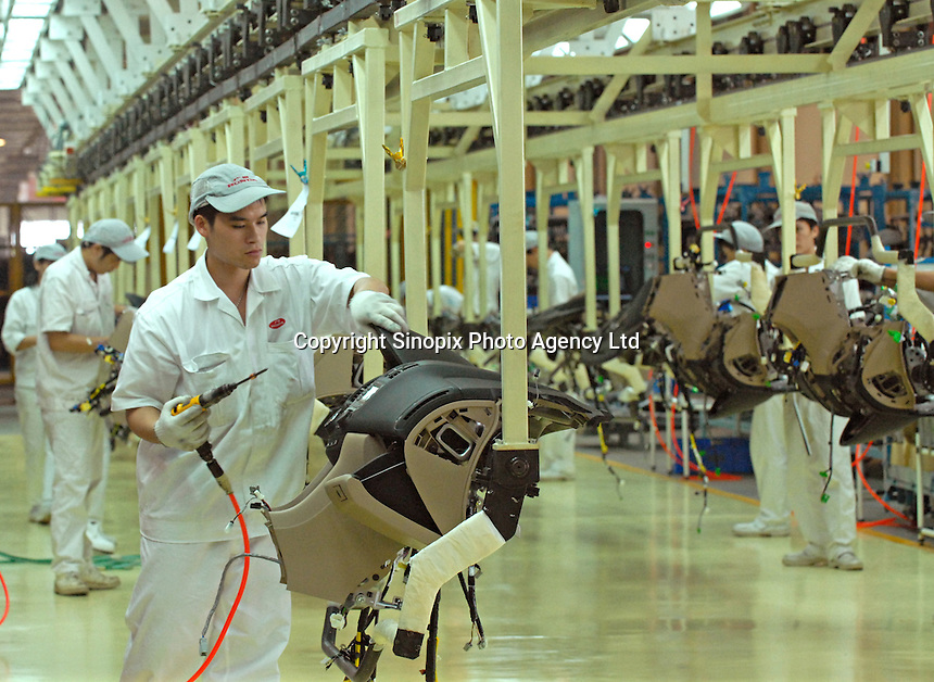 A worker on the internal navigation / cock-pit production line of the Honda Accord at the new Guangzhou Honda Automobile Co. Ltd factory. The plant built at a cost of 140 million US$ is one of the most advanced car plants in the world. It has a state of the art production line as well as the world's first total water re-cycling sytem..