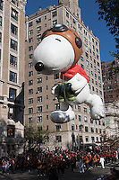NEW YORK - NOVEMBER 24:  The Snoopy the Flying Ace helium filled balloon floats overhead during the annual Macy's Thanksgiving Day Parade on Thursday, November 24, 2011.