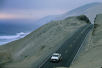 A lone vehicle drives along the desert Coastal Road hugs the cliff and cuts through sand dunes along this desolate part of the Pan American hiway in Peru.