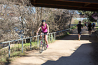 Young Woman athlete Riding Bike under bridge passing runners and joggers on the Lady Bird Lake Hike and Bike Trail on Town Lake Austin, Texas.