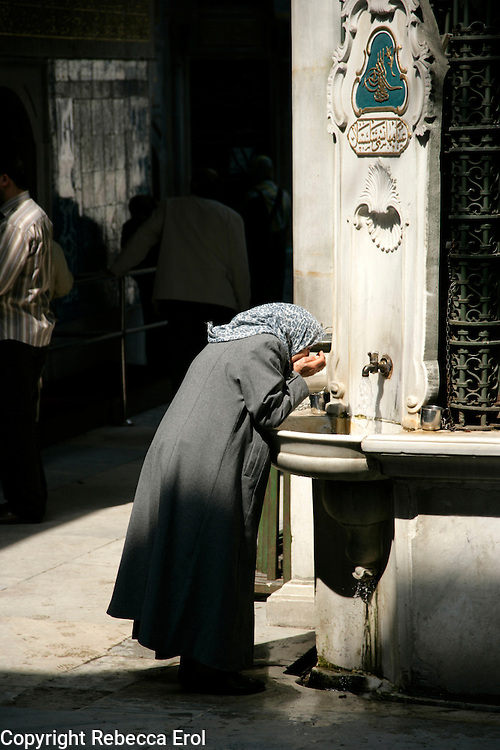 LADY DRINKING WATER AT THE EYUP MOSQUE COMPLEX, ISTANBUL, TURKEY