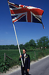 Wishford Magna, Wiltshire. 1980s<br /> Oak Apple Day May 29th the Union Jack flag is carried at the head of the Grovely Forest Right procession around the village, the flag bearer wears in his buttonhole a sprig of Oak Apples. They are celebrating the right to collect wood from the Grovely forest and also the Battle of Worcester in 1651 when King Charles II escaped the Roundheads by hiding in an oak tree near Boscobel.