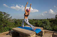 Young woman stretches yoga tree pose, sunset meditation silhouette on Mount Bonnell overlooking the downtown Austin, Skyline. Motivation inspiration, sport and fitness stretching exercising outdoors in nature.