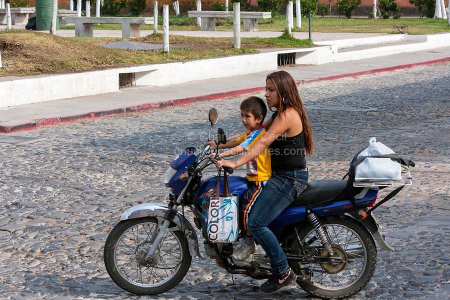 Antigua, Guatemala.  Woman and Young Boy on Motorbike, no Helmet.