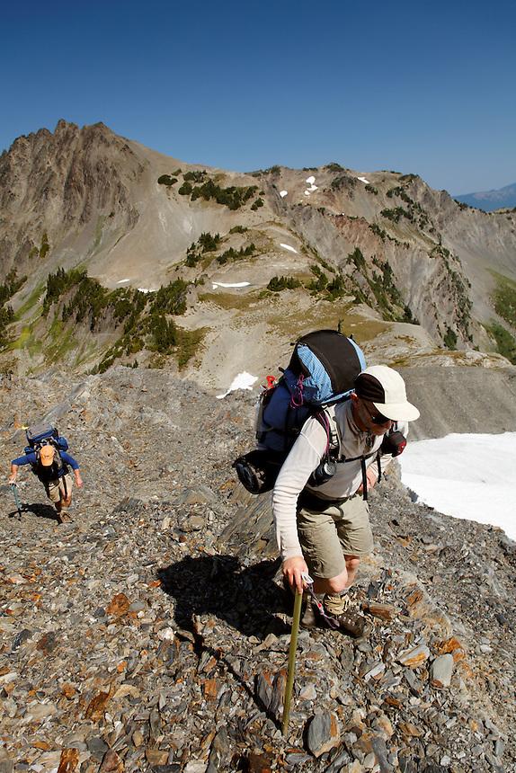 Backpackers scrambling up rock ridge, Bailey Range Traverse, Olympic Mountains, Washington