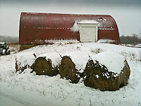Apple iPhone photo of snow covered barn and rolls of hay on a farm.