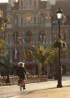 Cyclist outside Antwerp town hall, Antwerp, Belgium