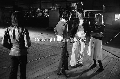 """Paul and Linda McCartney Wings Tour 1975. Paul and Linda talking to Denny Laine. They have just had an official Wings group photograph taken. Elstree rehearsal studio London England.. The photographs from this set were taken in 1975. I was on tour with them for a children's """"Fact Book"""". This book was called, The Facts about a Pop Group Featuring Wings. Introduced by Paul McCartney, published by G.Whizzard. They had recently recorded albums, Wildlife, Red Rose Speedway, Band on the Run and Venus and Mars. I believe it was the English leg of Wings Over the World tour. But as I recall they were promoting,  Band on the Run and Venus and Mars in particular."""
