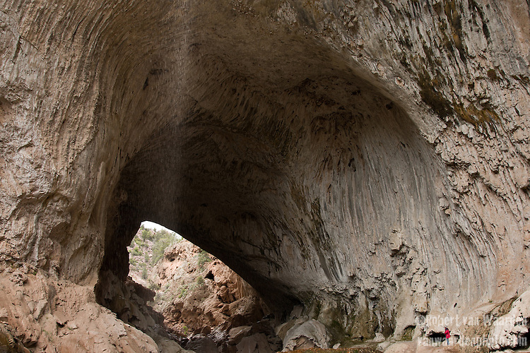 A figure stands under Tonto Bridge while water falls from above. Central Arizona, United States of America,
