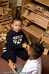 Education preschoool children ages 3-5 conflict argument two boys struggle over possession of toy vertical one boy using words