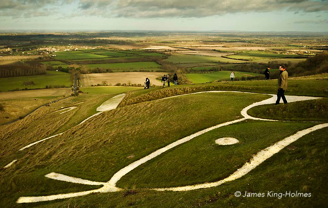 Visitors to the Uffington White Horse on New Year's Day 2013, showing a detail of the head of the gigantic chalk figure of a horse dating from the late Bronze Age. The trenches which form the figure are filled with chalk and are regularly scoured to maintain the high visiblilty.