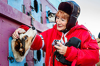 Volunteer security guard Deirdre Wilson of Sydney Australia pets a Cindy Abbott dog just prior to the Ceremonial Start in Anchorage on Saturday March 4, 2017 <br /> <br /> Photo by Jeff Schultz/SchultzPhoto.com  (C) 2017  ALL RIGHTS RESVERVED