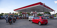 Yogyakarta, Java, Indonesia.  Motorbikes and Cars Lining Up for Fuel at Local Gas Station.