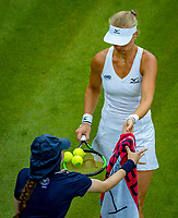 London, England, 4 th. July, 2018, Tennis,  Wimbledon, Womans singles second round, Kiki Bertens (NED) receives balls from a ballgirl<br /> Photo: Henk Koster/tennisimages.com