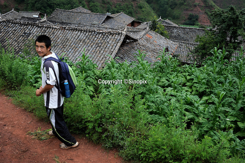 Miao Yun Fei, 16, treks to Honggi Village in the mountains of Sichuan Province, China. The group of young boxers are hoping to make it to become some of China's first professional boxers...PHOTO BY SINOPIX
