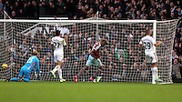Sunday 07 December 2014<br /> Pictured: Diafra Sakho (3rd L)of West Ham seals his team's win by making the score 3-1 to his team, replacement Swansea goalkeeper Gerhard Tremmel (L) fails to save the ball.<br /> Re: Premier League West Ham United v Swansea City FC at Boleyn Ground, London, UK.