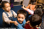 Educaton preschool  3-4 year olds movement dancing exercise group of children dancing to music moving with hands on each other's shoulders  horizontal