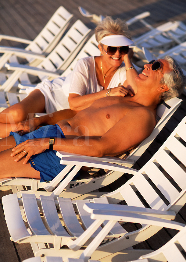 Retired couple in deck chairs on cruise ship
