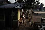 As the sun rises in the distance, a man smokes a cigarette outside his shop in Relocation Golden Valley in Barangay Pagkakaisa outside of Puerto Princesa, Palawan in the Philippines. <br /> Photo: Sanjit Das/Panos for Greenpeace