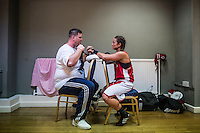 Emily Williams and her trainer prepare for her fight against Harvinder Jutteat the London Irish Centre where the 'Carpe Diem' white collar boxing event is taking place. <br /> <br /> 'White-collar boxing' is a growing phenomenon amongst well paid office workers and professionals and has seen particular growth in financial centres like London, Hong Kong and Shanghai. It started at a blue-collar gym in Brooklyn in 1988 with a bout between an attorney and an academic and has since spread all over the world. The sport is not regulated by any professional body in the United Kingdom and is therefore potentially dangerous, as was proven by the death of a 32-year-old white-collar boxer at an event in Nottingham in June 2014. The London Irish Centre, amongst other venues, hosts a regular bout called 'Carpe Diem'. At most bouts participants fight to win. Once boxers have completed a few bouts they can participate in 'title fights' where they compete for a replica 'belt'.