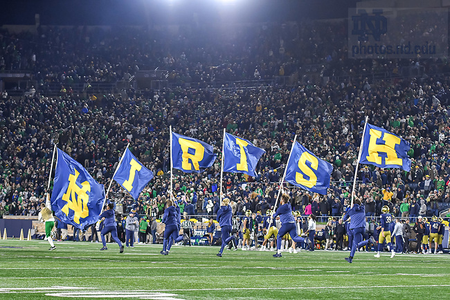 October 23, 2021; Cheerleaders carry flags after a touchdown, game day, 2021. (photo by Matt Cashore)