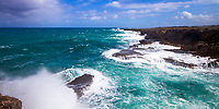 Wild Archers Bay coastline with huge, turquoise Caribbean Sea waves crashing on the rocks under a blue sky with dramatic clouds, in Barbados Island