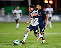 LAKE BUENA VISTA, FL - JULY 26: Russell Teibert of Vancouver Whitecaps FC dribbles away from Roger Espinoza of Sporting KC during a game between Vancouver Whitecaps and Sporting Kansas City at ESPN Wide World of Sports on July 26, 2020 in Lake Buena Vista, Florida.