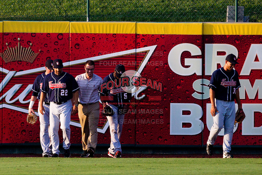 Travis Witherspoon (5) of the Arkansas Travelers walks back toward his position in center field with the Travelers trainer and Manager Mike Micucci (22) during a game against the Springfield Cardinals at Hammons Field on July 24, 2012 in Springfield, Missouri. Witherspoon would remain in the game after crashing into the center field wall while making a leaping catch. (David Welker/Four Seam Images)